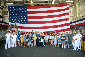 170804-N-GG858-221 SEATTLE (August 4, 2017) Members from the Rotary Club of Seattle take a group picture in the hangar bay of San Antonio-class amphibious transport dock ship USS Anchorage (LPD 23) during the 68th Annual Seafair Fleet Week in Seattle. Seafair Fleet Week is an annual celebration of the sea services wherein Sailors, Marines and Coast Guard members from visiting U.S. Navy and Coast Guard ships and ships from Canada make the city a port of call. (U.S. Navy photo by Mass Communication Specialist 2nd Class Matthew Dickinson/RELEASED)